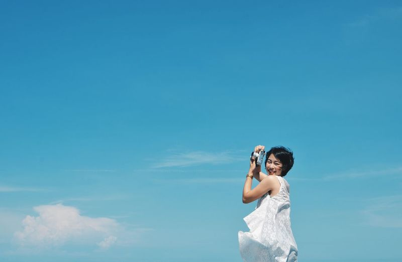 Happy Asian woman with vintage camera,travel concept. Blue Camera - Photographic Equipment Day Leisure Activity Lifestyles Nature One Person Outdoors People Photographing Photography Themes Real People Sky Standing Technology Young Adult Young Women