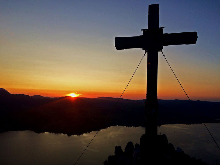 Silhouette cross on lake against sky during sunset