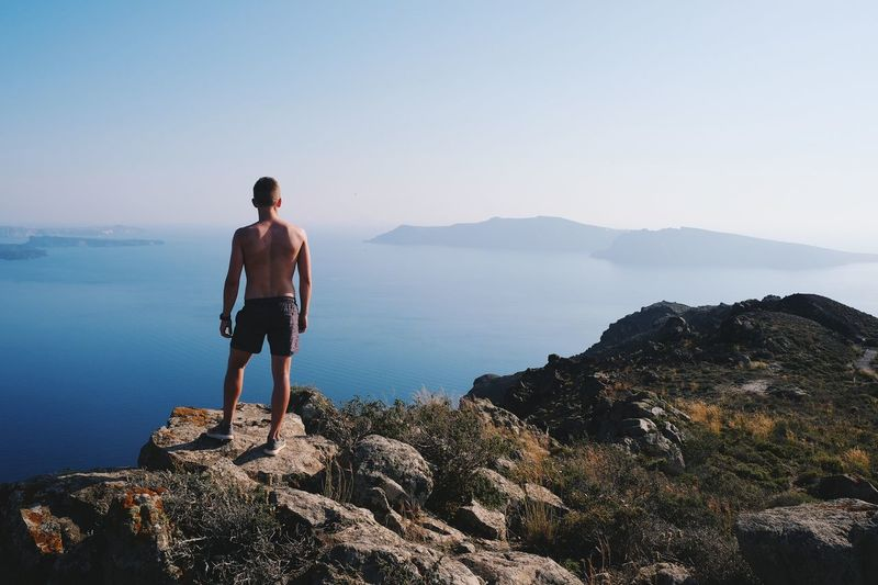 Real People Rock - Object Full Length Nature One Person Leisure Activity Scenics Standing Beauty In Nature Lifestyles Sea Rear View Exploration Mountain Tranquility Day Adventure Shirtless Outdoors Men