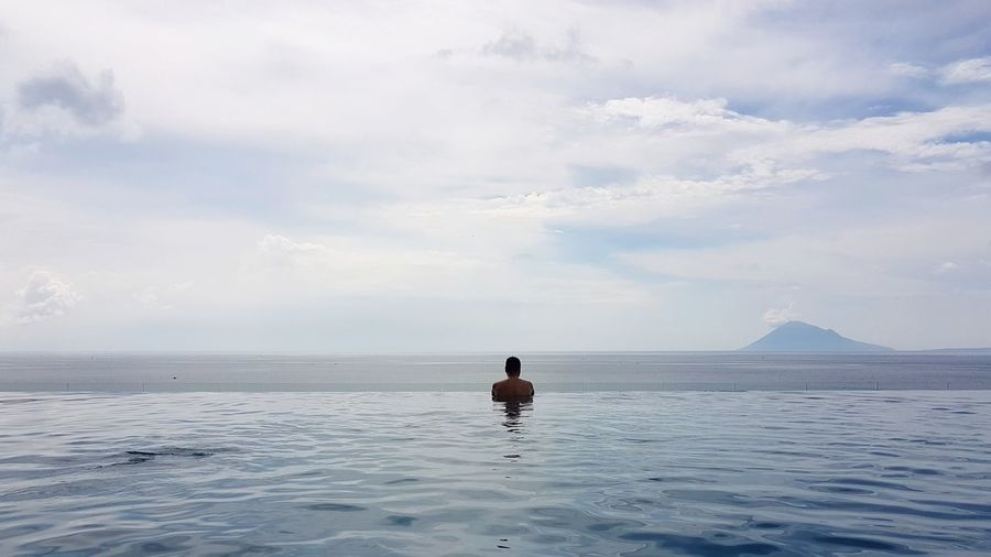 Rear view of man by sea in infinity pool