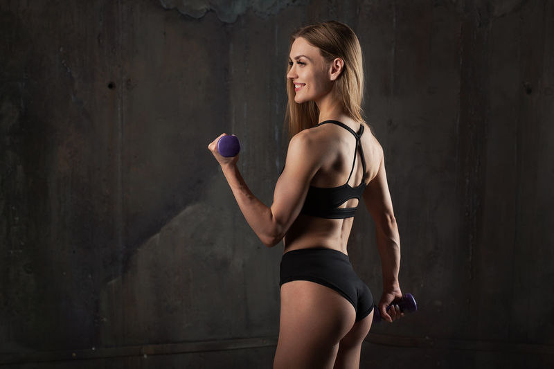 Young woman in bikini exercising while standing against wall