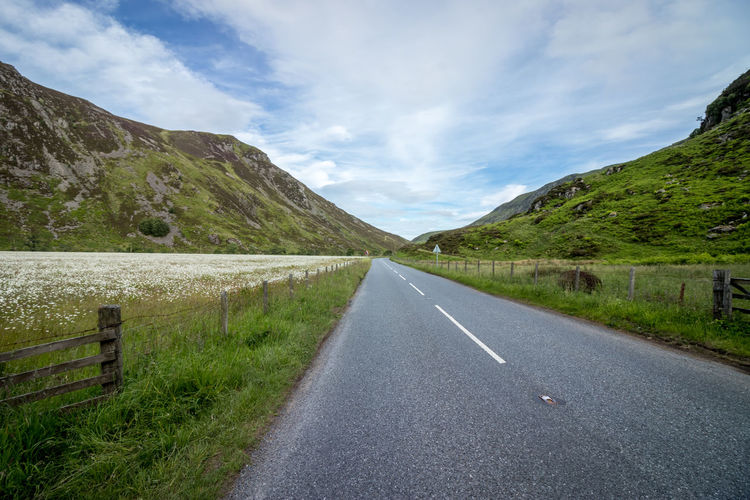 route in the highlands Highlands Scotland United Kingdom Flower Field Mountain Road Winding Road Summer Water Rural Scene Sky Landscape Cloud - Sky Empty Road vanishing point Road Marking Dividing Line Passing Mountain Road Countryside Mountain Range Country Road