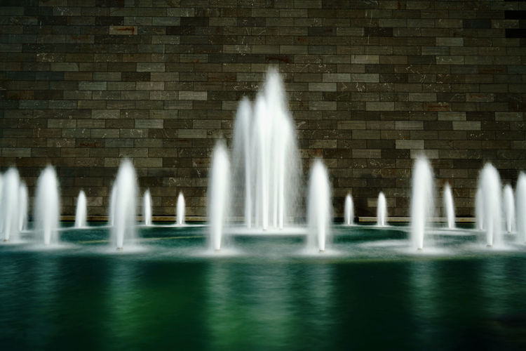 Water splashing on fountain against wall