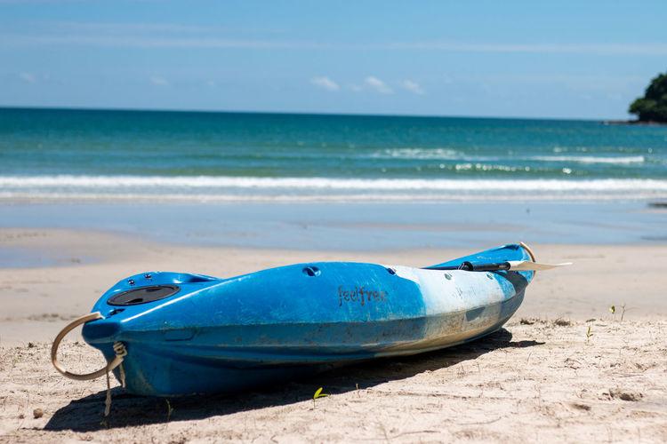 Boat on beach against blue sky