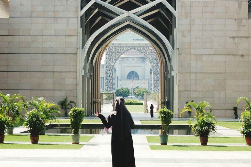 Rear view of woman in burka standing in front of tuanku mizan zainal abidin mosque