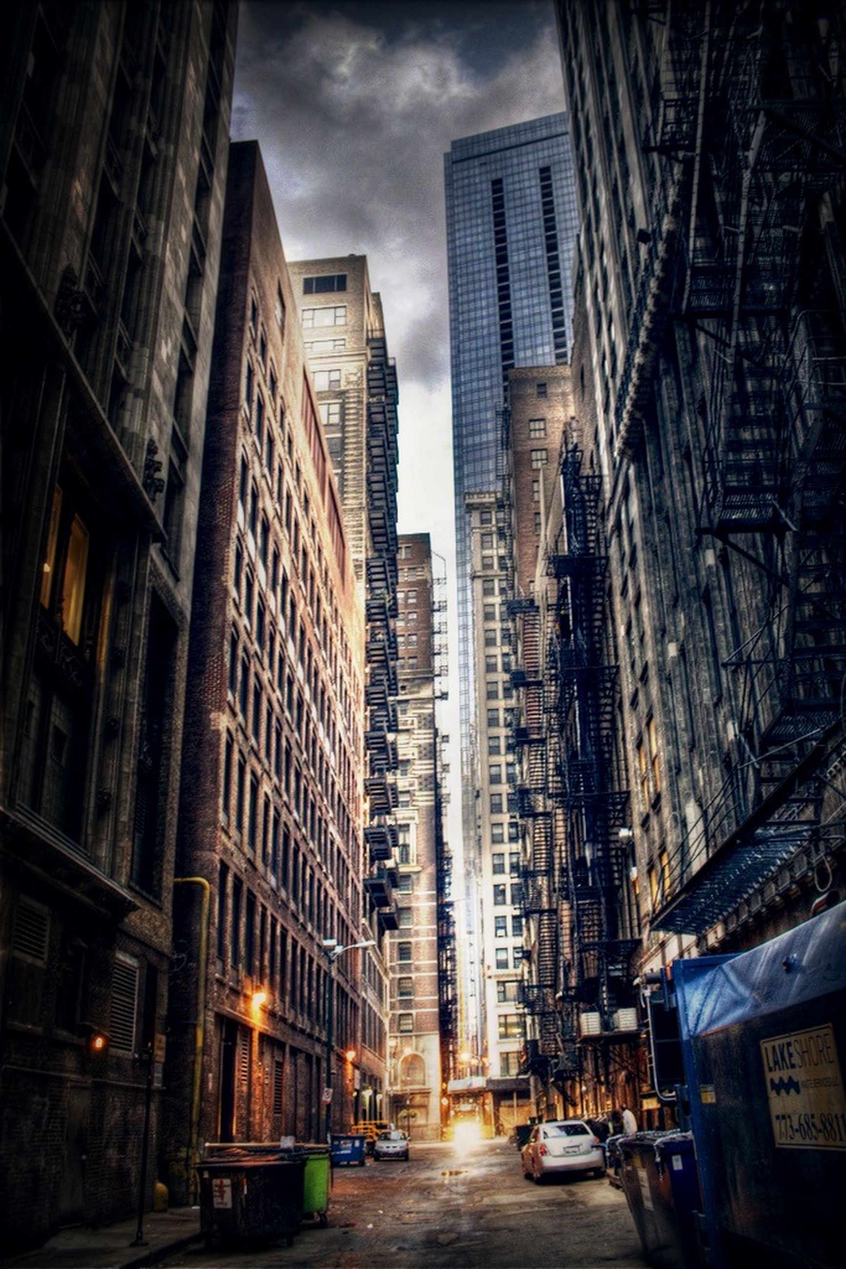 building exterior, architecture, city, built structure, street, car, skyscraper, transportation, sky, land vehicle, road, building, office building, city life, the way forward, tall - high, modern, city street, illuminated, residential building