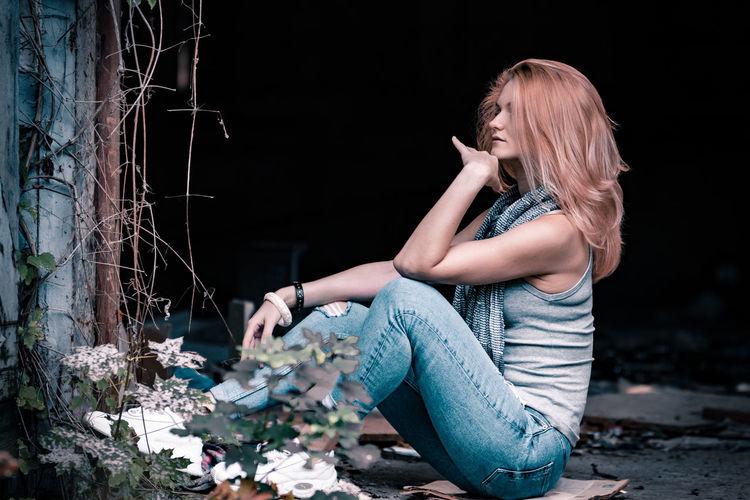 Beautiful young looking away woman sitting outdoors