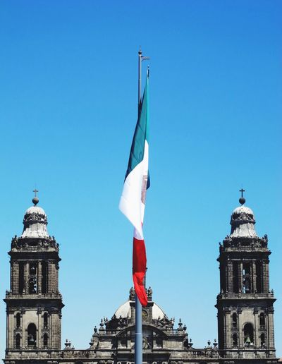 Mexican flag by metropolitan cathedral against clear blue sky