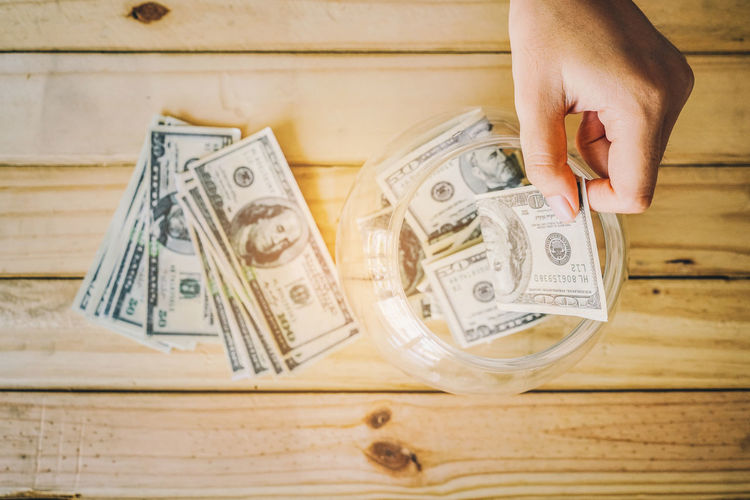 Allocate funds for the future. Holding Hands Jidpipat_Photo Adult Banknote Business Close-up Currency Day Dollar Economy Finance Hand High Angle View Holding Human Body Part Human Hand Indoors  Leisure Activity Making Money One Person Paper Currency Saving Money Savings Wealth Wood - Material