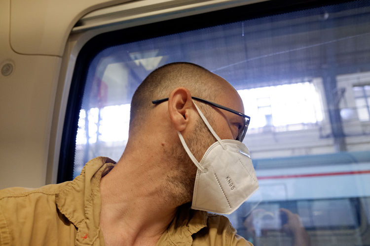 Close-up of man wearing mask looking away while sitting in train