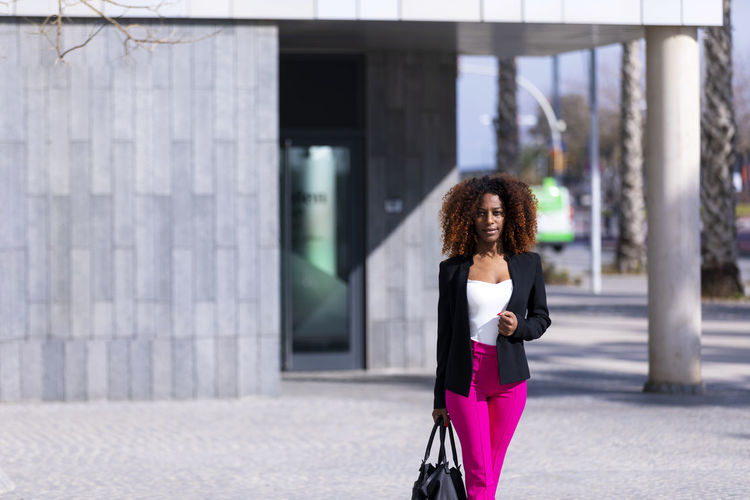 Front view of young beautiful curly woman wearing elegant clothes and handbag while standing in the street in sunny day One Person Women Curly Hair Architecture Young Adult Young Women Hairstyle Hair Building Exterior Built Structure Day Real People Adult Standing Lifestyles Leisure Activity Focus On Foreground City Fashion Outdoors Architectural Column Beautiful Woman Standing Posing Model Handbag  Afro African American Smiling Laughing Looking At Camera Looking Away Elegant Attractive Bussinesswoman Empowered City Life Urban Walking Beautiful Pink