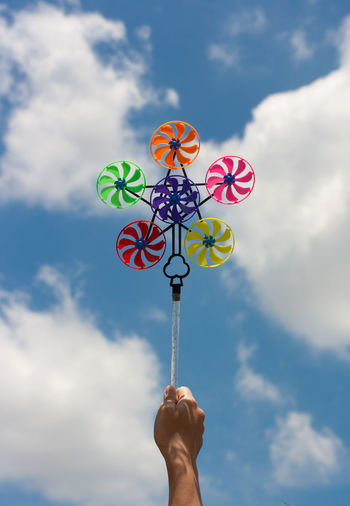Cropped hand holding colorful pinwheel toy against sky