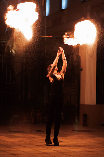 Full length of man standing by fire at night