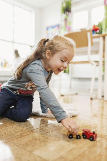 Happy girl playing on floor