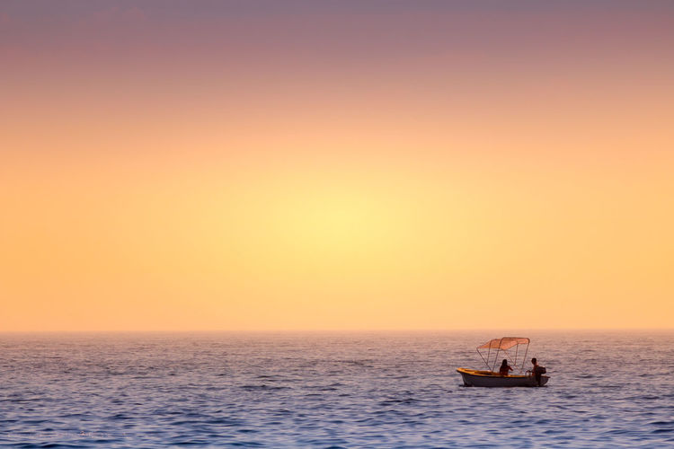 Scenic view of sea and boat with couple against sky during sunset