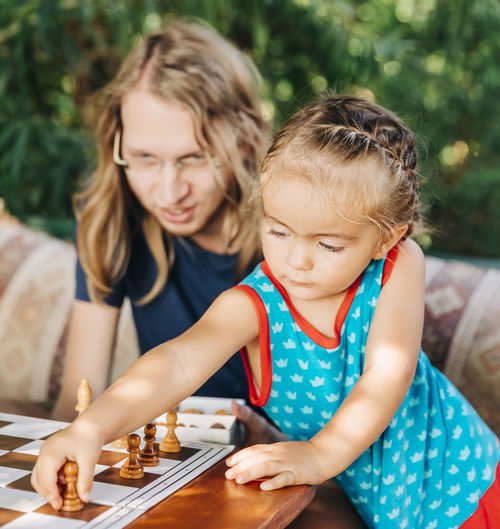Mother looking at girl playing chess in yard