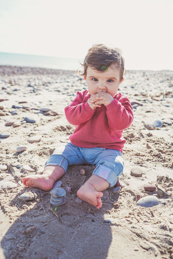 Happy boy sitting on beach