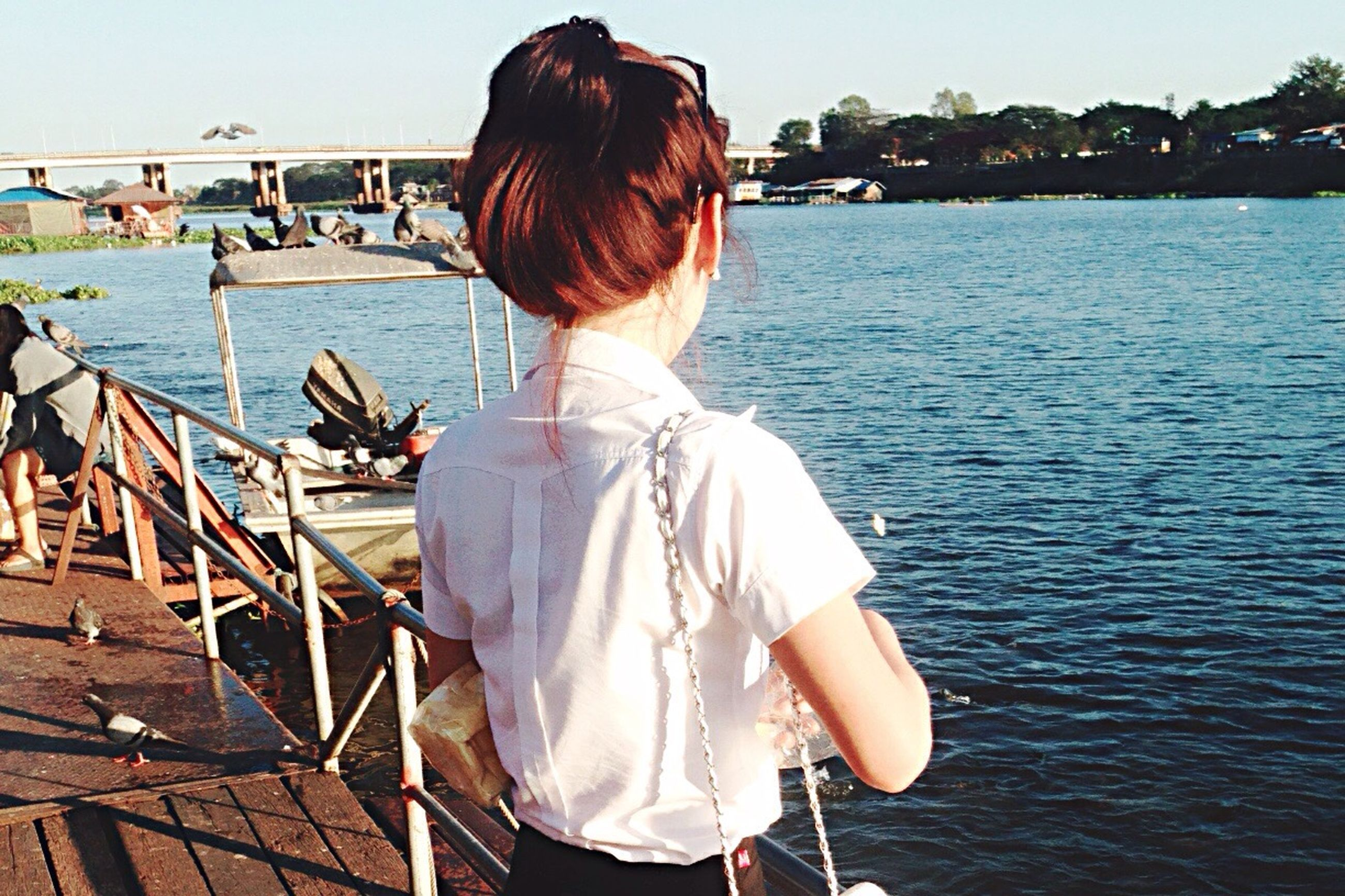 water, rear view, lifestyles, leisure activity, sea, casual clothing, long hair, young adult, person, sitting, standing, full length, three quarter length, young women, clear sky, railing, lake