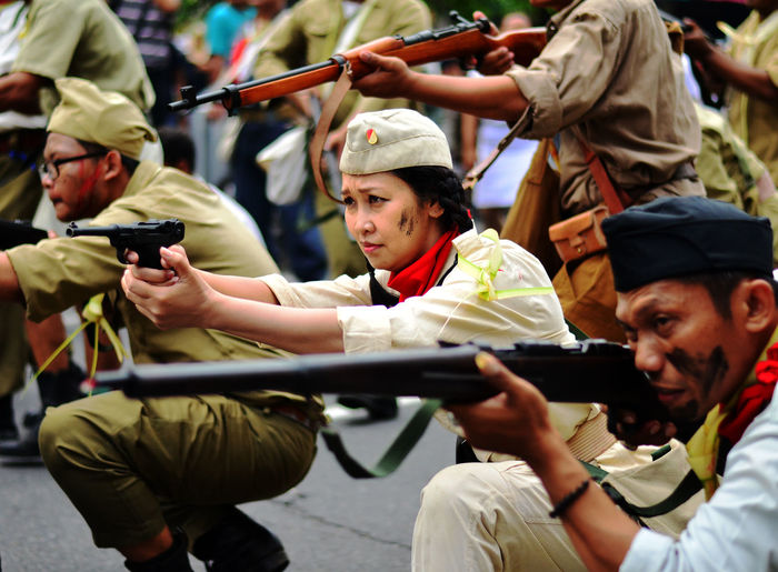 Police force aiming guns on road