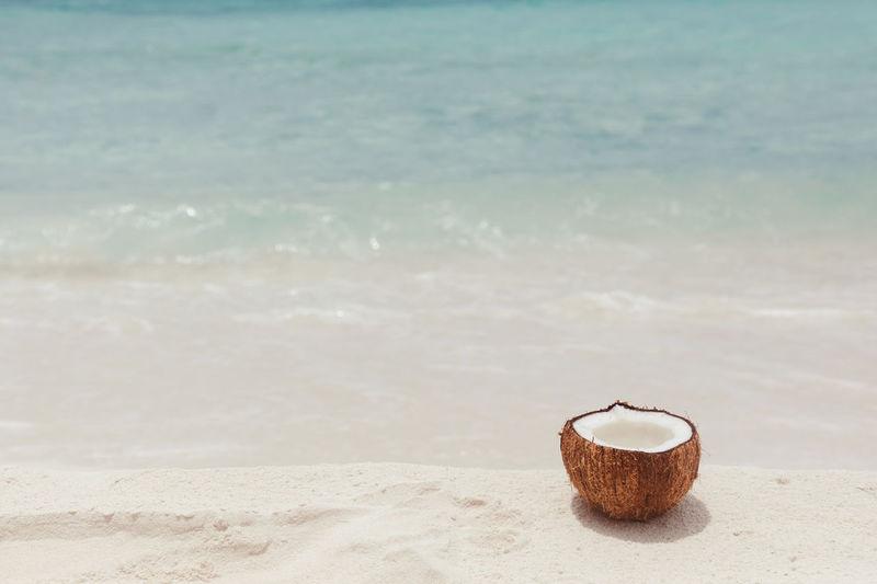 Deck chair on sand at beach against sky