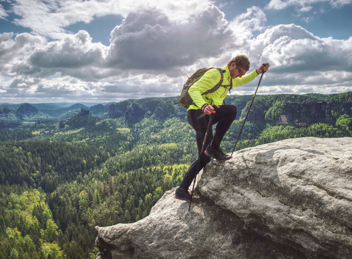 Man backpacker running up on mountain top cliff edge. travel and trail lifestyle concept adventure
