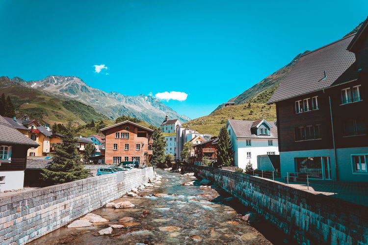 Canal flowing amidst buildings by mountains against blue sky