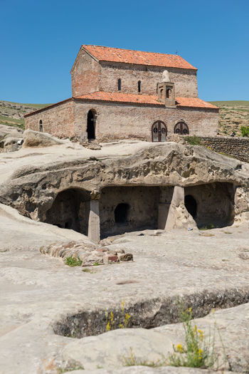 GEORGIA. UPLISTSIKHE CAVE TOWN - JUNE 13, 2017: Tourists walks through the cave city. The oldest stone church is built in the highest point of the city. Ancient Antique Archeology Church Georgia Lost Ruins Uplistsikhe Ancient Civilization Architecture Building Exterior Built Structure Cave City Cave Town Civilization Clear Sky History Old Ruin Outdoors Rocks Sky Stone Temple Travel Destinations Tree
