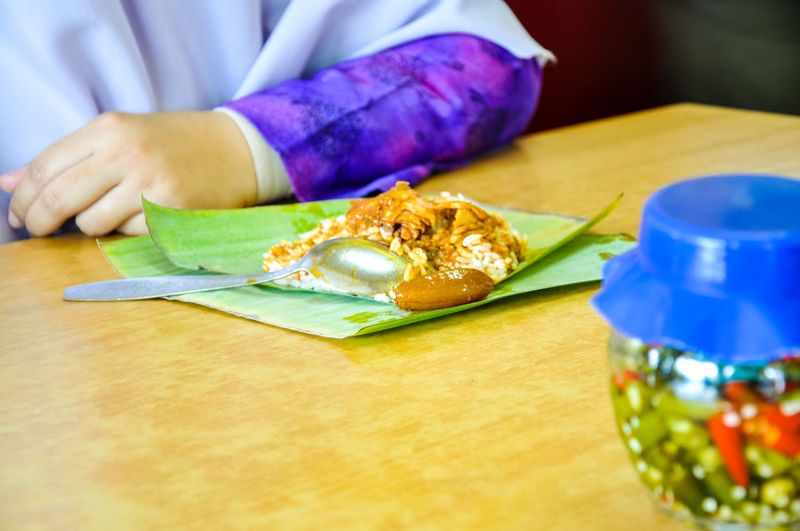 Cropped Hand Of Woman With Rice With Vegetable Served On Banana Leaf
