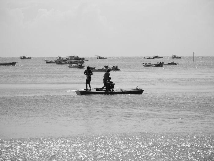 Fishermen on boat in sea against sky