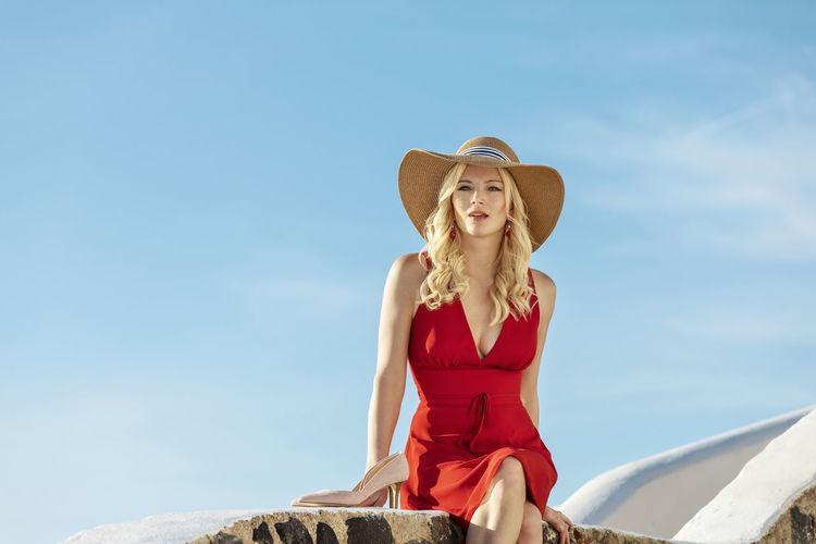 Woman wearing hat sitting against blue sky