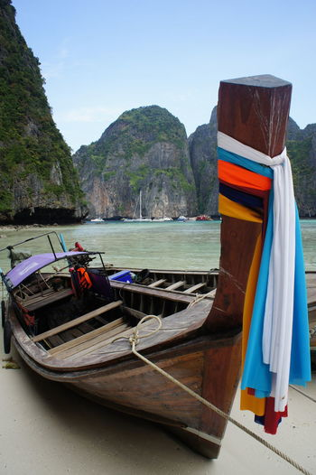 Fabrics Tied To Longtail Boat Moored On Shore