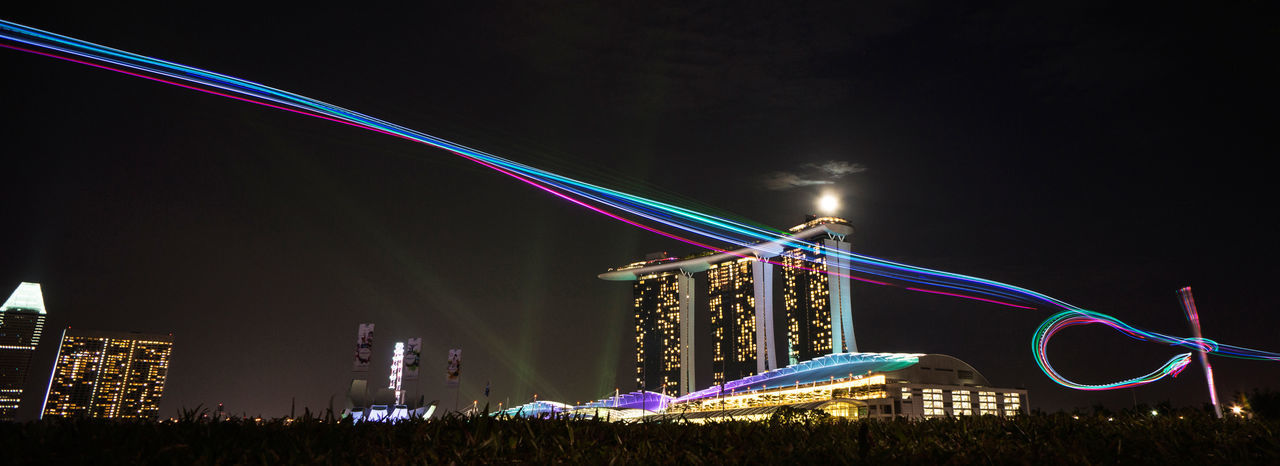Panoramic View Of Light Trails Against Illuminated Marina Sands Bay