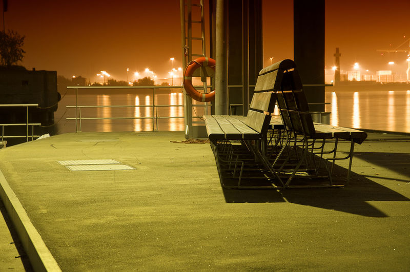 Life belt on structure by benches at harbor against elbe river