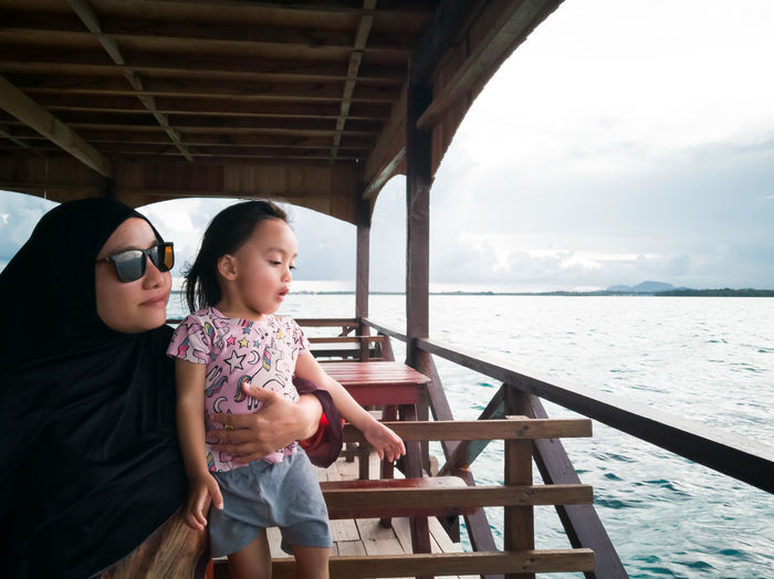 Mother with daughter looking at sea from boat