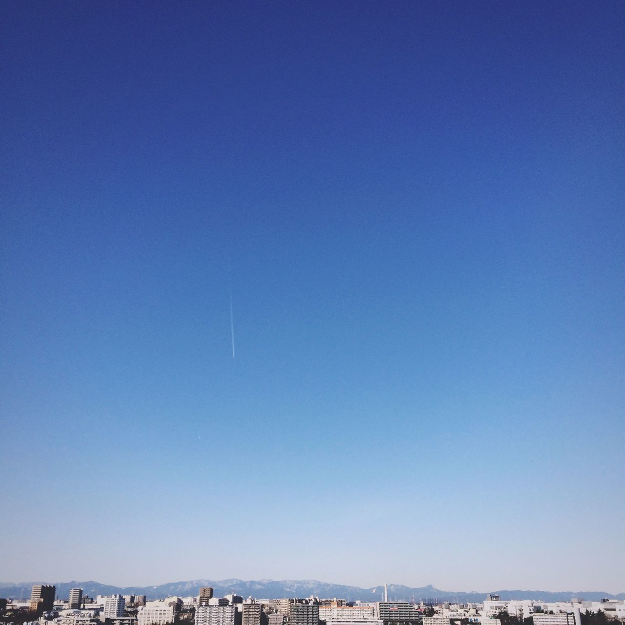 clear sky, blue, copy space, architecture, building exterior, cityscape, city, no people, outdoors, built structure, airplane, day, vapor trail, scenics, nature, flying, beauty in nature, sky, contrail