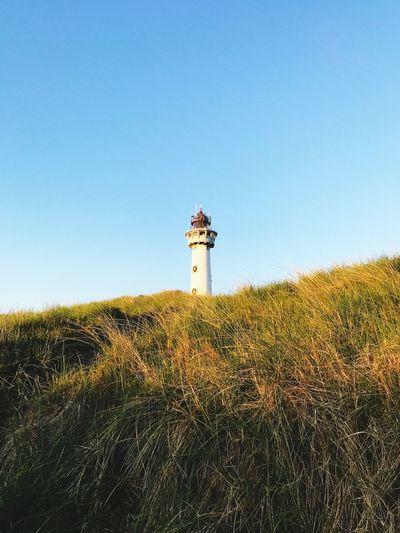 Lighthouse on field against clear sky