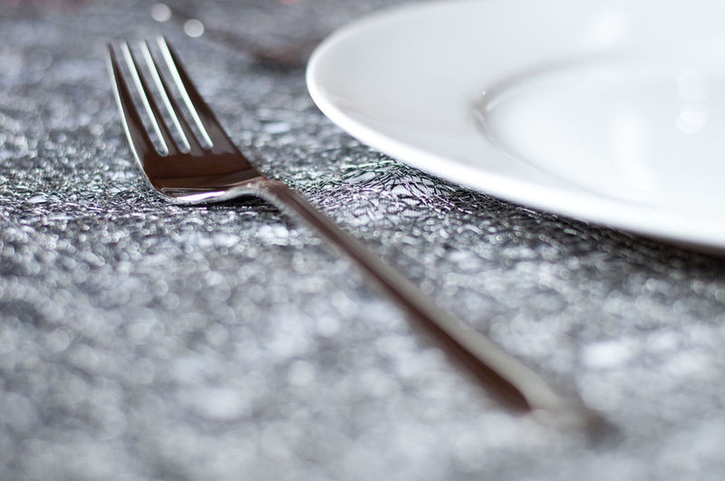 Close-up of fork and plate on textured table