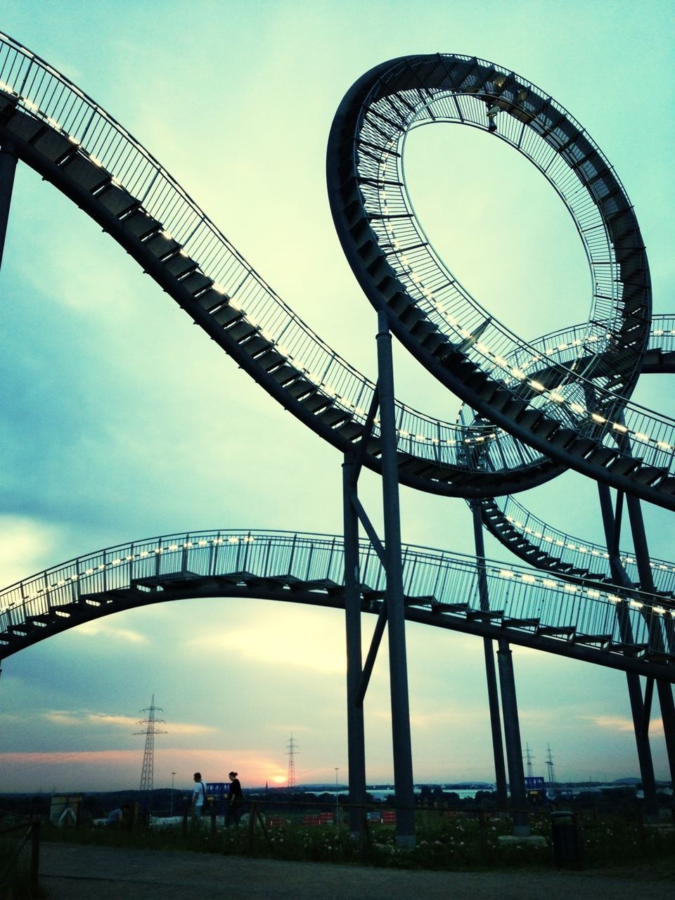 arts culture and entertainment, built structure, low angle view, amusement park, architecture, outdoors, bridge - man made structure, day, sky, large group of people