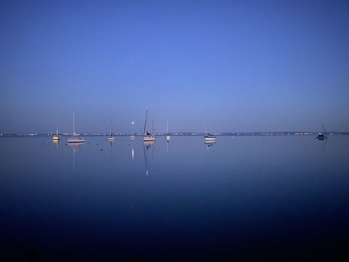 Sailboats in sea against clear blue sky