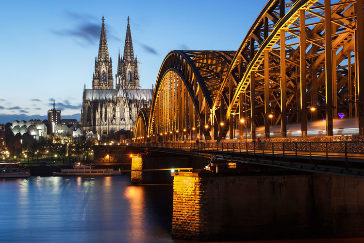 Cathedral of cologne and Hohenzollern bridge with moving train Architecture Bridge Cathedral City Cityscape Cologne Dusk Illuminated Landmark Lights Night No People Orange Outdoors Rhine River Train Travel Urban Skyline Water Köln Hohenzollernbrücke