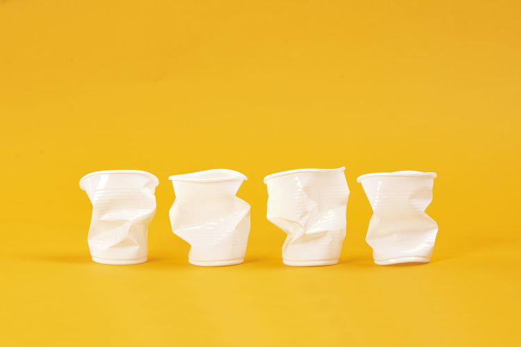 Three disposable plastic cups Disposable Cup Plastic Broken Recycling Garbage Environmental Conservation Mug Disposable Take Out Coffee Cup Pollution Environment Protection Environmental Damage Problems Global Warming Eco Ecology Environment Care Earth Ecosystem  Nature Environmental Issues Concept Collection Group Of Objects Next To In A Row Colored Background Yellow Photography Yellow Background