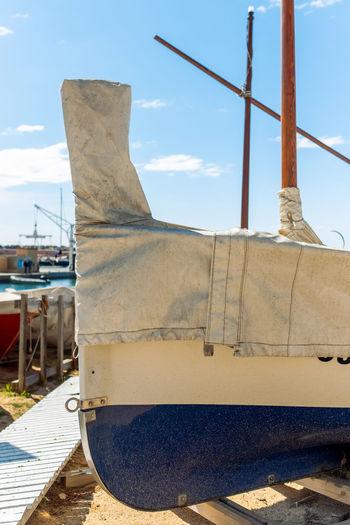Sailboats moored at shore against sky