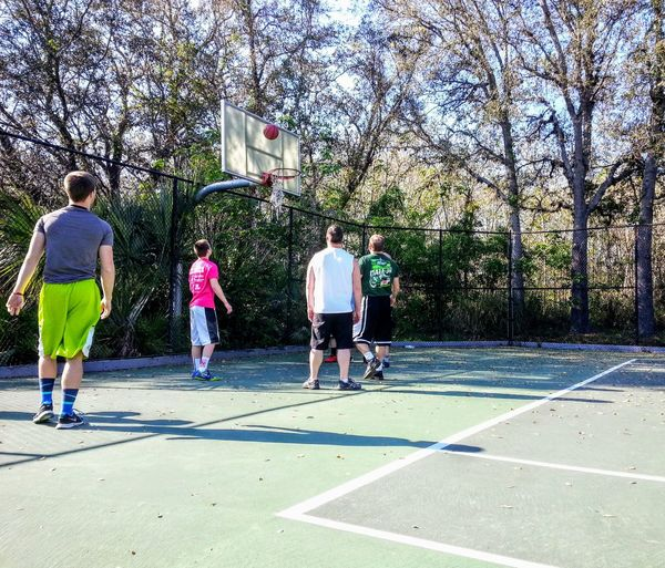 Group of people playing basketball court