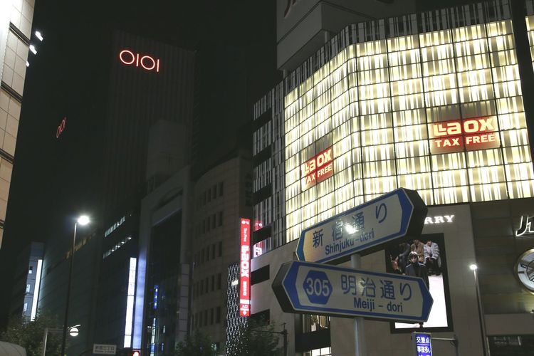 Low angle view of illuminated text in city at night