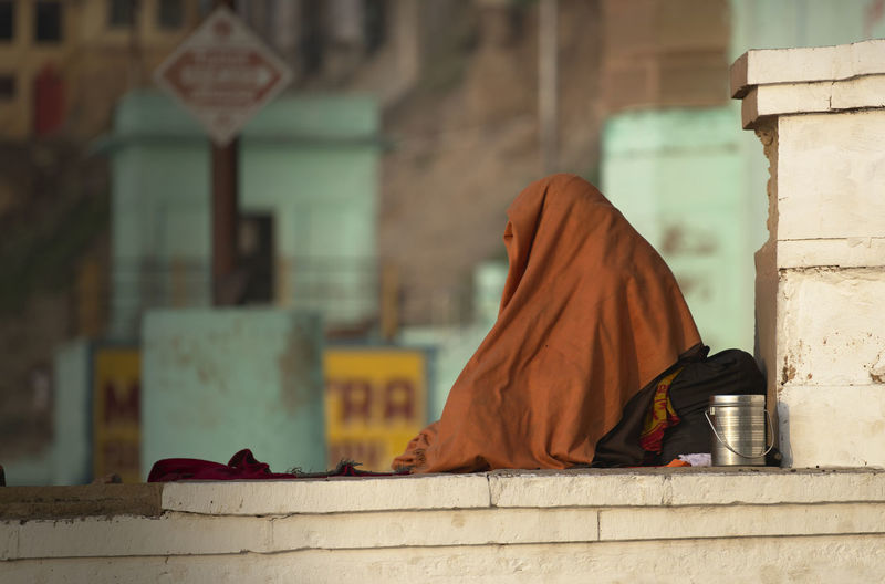 Person covering blanket sitting outside temple