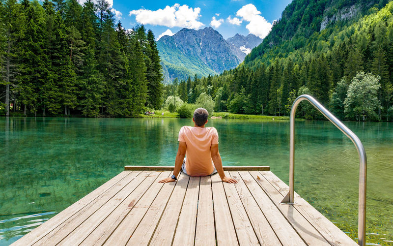 Rear view of young man sitting on deck by lake in mountains.