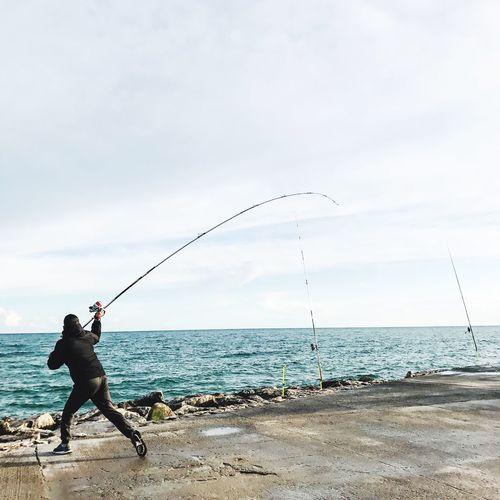 Full length of man fishing on promenade by sea against sky