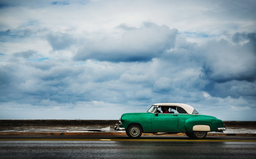 Vintage car on road against cloudy sky