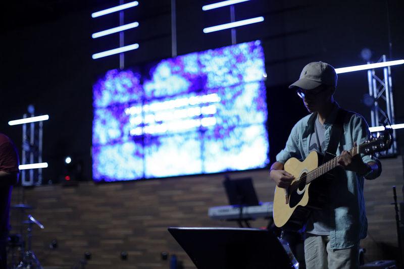 Man playing guitar on illuminated stage at night