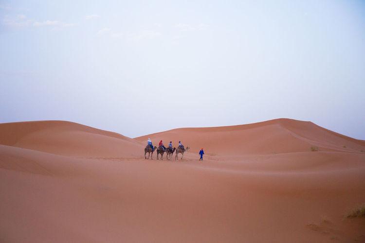 People Walking In Desert Against Sky